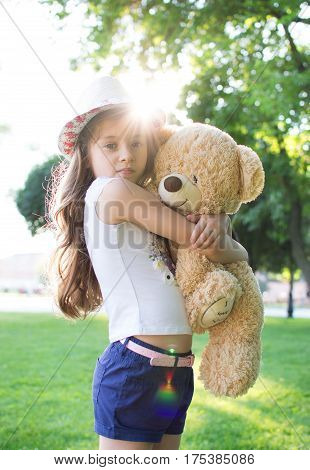 Little cute girl in the wicker hat stands in a park on the grass hugging her teddy bear heavily. Photo against the sun. Best friend. Solar flare.