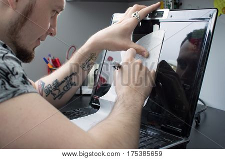 Creating A Tattoo Close-up. The Artist Circled The Pen With A Tattoo Sketch On The Monitor Of His La