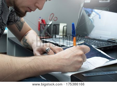 Making A Close-up Tattoo. An Artist With A Beard Draws A Sketch Of A Tattoo At His Workplace. Draw.