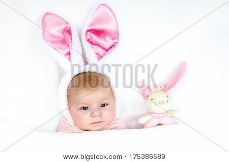 Adorable cute newborn baby girl in Easter bunny costume and ears. Lovely child playing with plush rabbit toy. Holiday concept.
