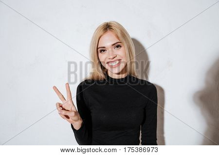 Portrait of a smiling happy woman showing peace sign and looking at camera isolated on the white background