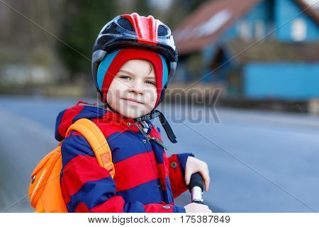 Cute little preschool kid boy riding on scooter riding to school. children activities outdoor in winter, spring or autumn. funny happy child in colorful fashion clothes and with helmet. High speed