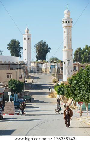 EL GOULA, TUNISIA - DECEMBER 02, 2011: Unidentified people walk by the street in the town of El Goula, Tunisia.