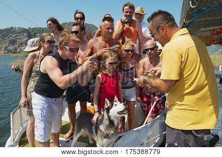 MUGLA, TURKEY - AUGUST 13, 2009: Unidentified tourists take photos of a crab demonstrated by a guide during river cruise by the Dalyan river in Mugla, Turkey.