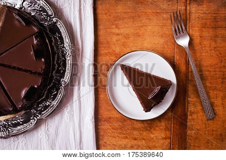 Amazing chocolate cake, ready to eat on wooden table, directly above