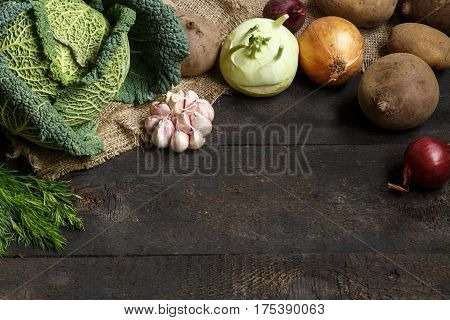 Spring vegetables on a dark background: Savoy cabbage, cauliflower, onion, garlic, kohlrabi, celery root dill. Place for text