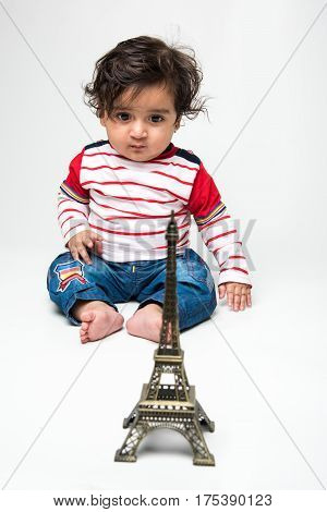 Indian baby boy with long hair sitting over white background with toy model or replica of eiffel tower
