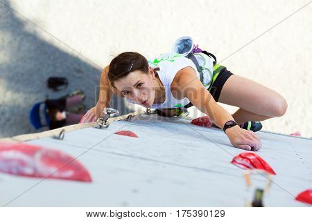 Beautiful female Climber moving up on vertical climbing Wall at qualification round of National Climbing Competitions. Dnipro, Ukraine, May 20, 2016