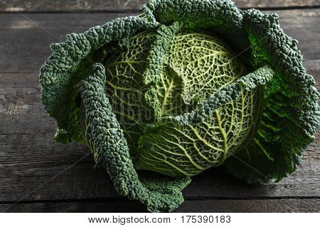 Savoy cabbage on a background of a dark wooden table.