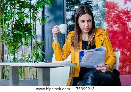 urban girl sit in cafe outdoor with coffee reading     magazine spring day city life concept