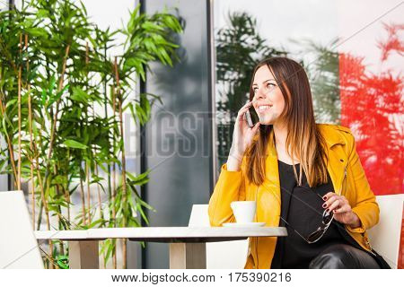 urban girl sit in cafe outdoor talking on smartphone spring day city life concept