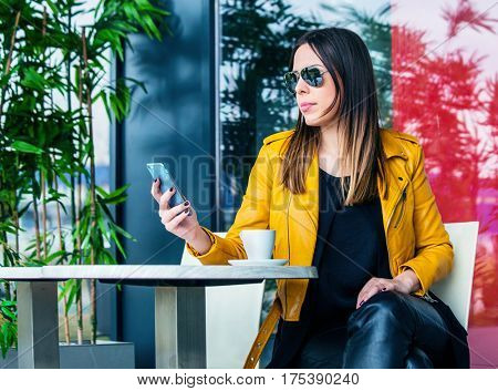 urban girl with sunglasses sit in cafe outdoor checking messages on smartphone spring day
