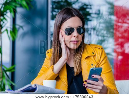 urban girl with sunglasses sit in cafe outdoor checking messages on smartphone spring day city life concept