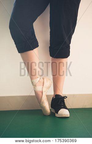 dancer girl feet one foot in sneakers other in ballet shoes closeup indoor shot