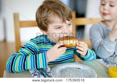 Adorable little preschool boy and girl eating sweet donut indoor. Child in domestic kitchen or in school canteen Cute kids and unhealthy sugared food