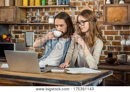 Young couple using laptop and drinking coffe in kitchen