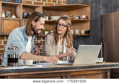 Attractive young couple working at home with laptop and documents