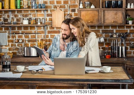 Attractive young couple sitting and hugging while working at home with laptop and digital tablet