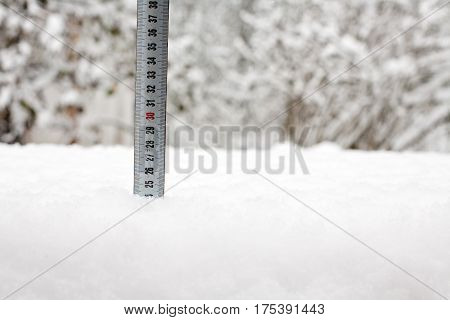 ruler tape measure in white snow cover closeup on winter outdoor background