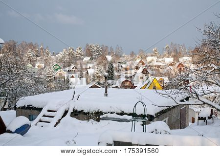 suburban settlement small wooden houses winter view on roofs covered by snow