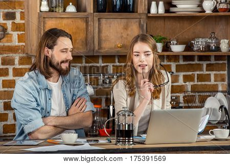 Young smiling couple of freelancers using laptop and drinking coffee at home