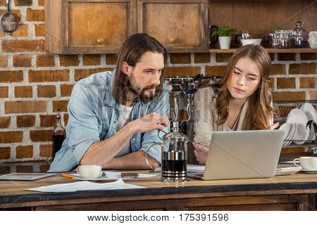 Young couple of freelancers using laptop on wooden table at home