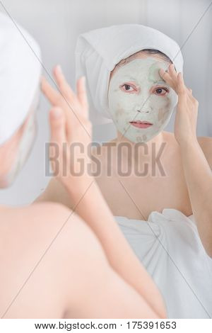 Woman Applying Mask On Her Face And Looking In The Mirror