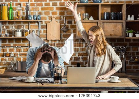 Angry young woman yelling at upset man and throwing documents