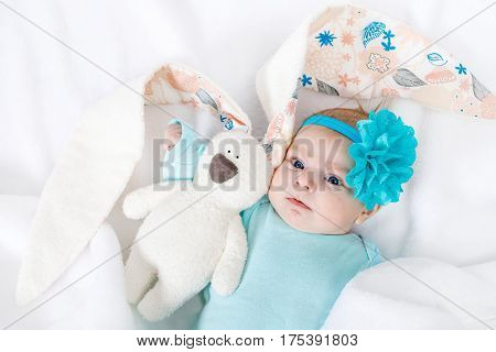 Adorable cute newborn baby girl with turquoise flower headband . Lovely child playing with plush rabbit toy wigh bit long ears. Holiday, Easter, childhood concept.