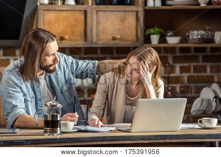 Young upset couple sitting with papers and laptop while working at home