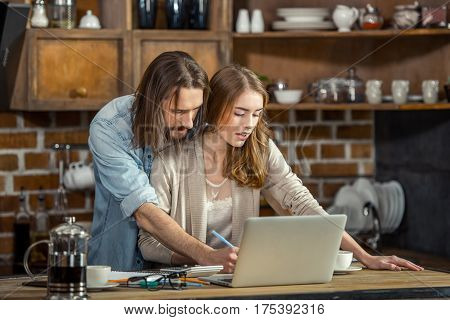 Young couple standing embracing while working together at home