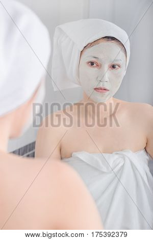 woman applying mask on her face and looking in the mirror in the bathroom