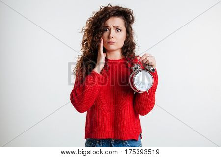 Upset young woman holding alarm clock and looking at camera over white background