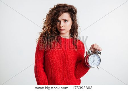 Portrait of a tired young woman holding alarm clock and looking at camera over white background