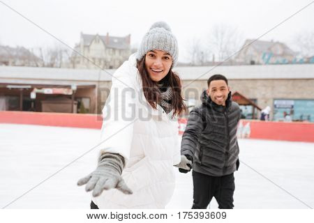 Cheerful young couple skating at outdoor rink in winter