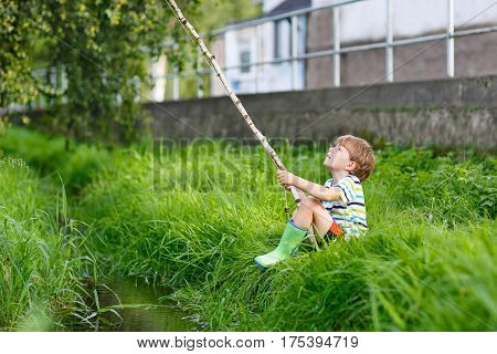 Active preschool kid boy fishing on a river with selfmade fishing rod  on sunny summer day. Happy child having fun. Active leisure for children outdoors.