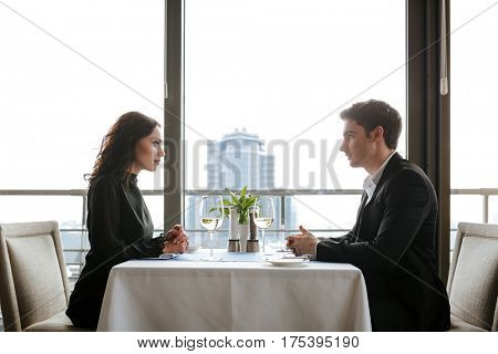Side view of young couple which sitting by the table in restaurant
