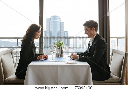 Side view of couple which sitting by the table in restaurant