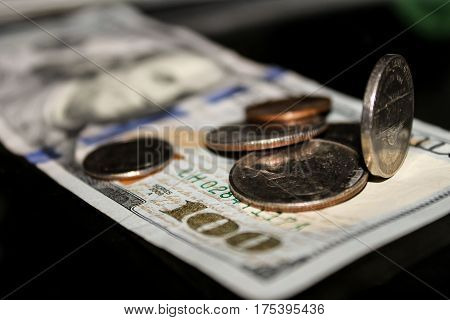 Variety of United States coins placed randomly on top of a lone, one hundred dollar bill.
