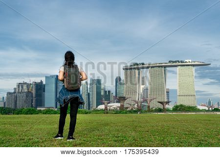 Asian woman traveler in Singapore looking at city view with backpack. Solo woman traveler backpacker in Singapore.