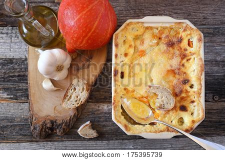 Vegetable pumpkin gratin with cheese in ceramic bakeware. Top view
