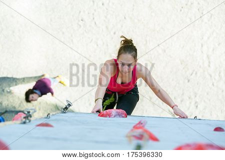 Junior female Athlete climbs Competition route and belaying referee watching her from below. Dnipro, Ukraine, May 20, 2016