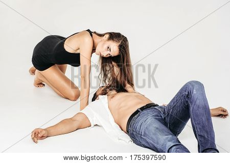 Pretty girl or sexy woman with long brunette hair in black undershirt crawls on knees to bearded man or brutal caucasian hipster in shirt with bare torso lying on floor isolated on white background