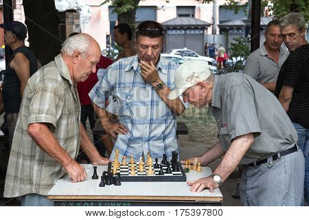 ODESSA UKRAINE - AUGUST 14 2015: Old men playing chess in a park of Odessa Ukraine