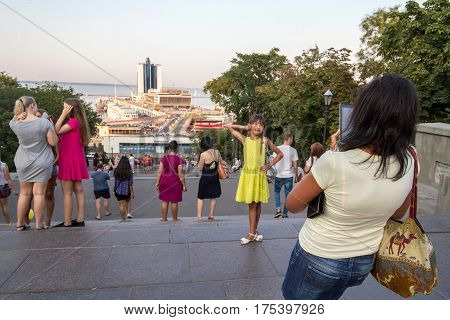 ODESSA UKRAINE - AUGUST 14 2015: Mother taking a picture of her daughter at the top of Potemkin stairs one of the landmarks of Odessa, Ukraine