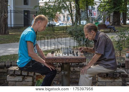 KIEV UKRAINE - AUGUST 17 2015: Old and young men playing chess in Taras Shevchenko Park kiev capital city of Ukraine