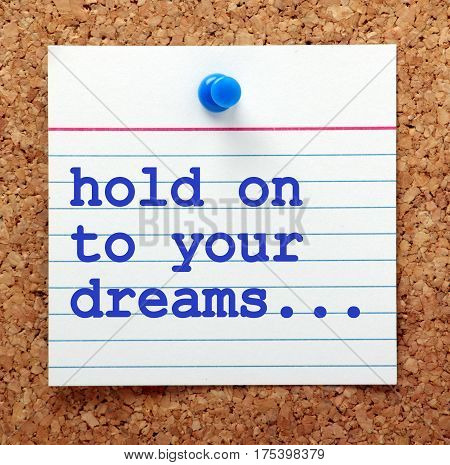 The words Hold On To Your Dreams on a note card pinned to a cork notice board as a reminder to maintain focus on your goals and aspirations