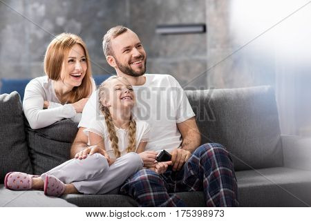Happy family sitting on sofa and watching tv together