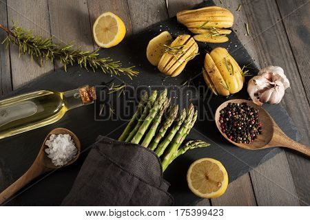 Food decoration with fresh green asparagus and ingredients on a black slate plate
