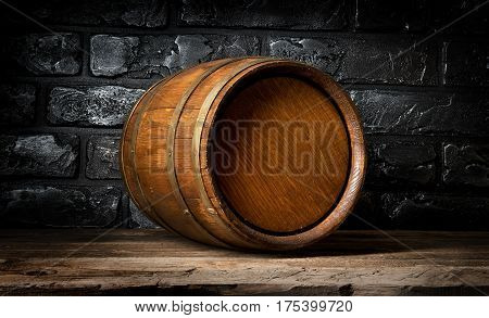 Brick wall and wooden barrel in cellar